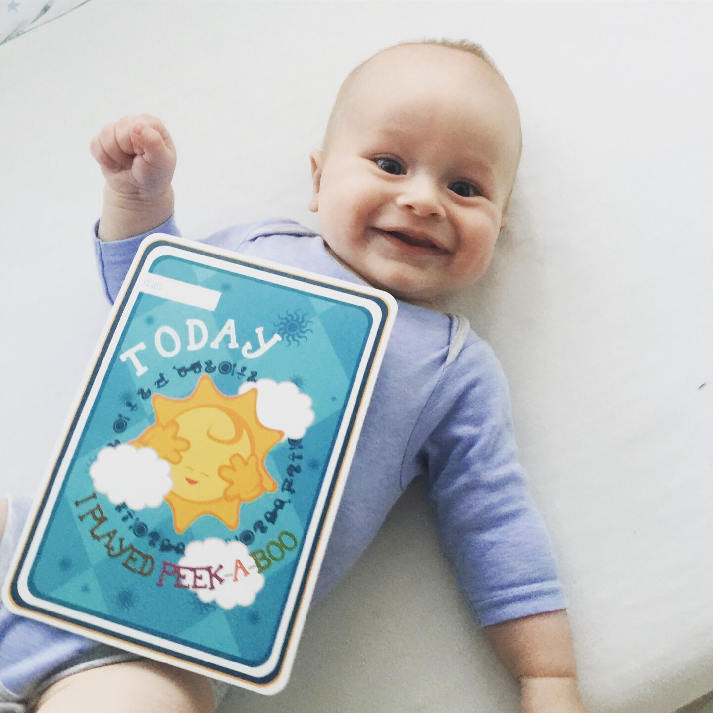 Dexter holding a milestone card that says 'Today I played peek-a-boo for the first time'