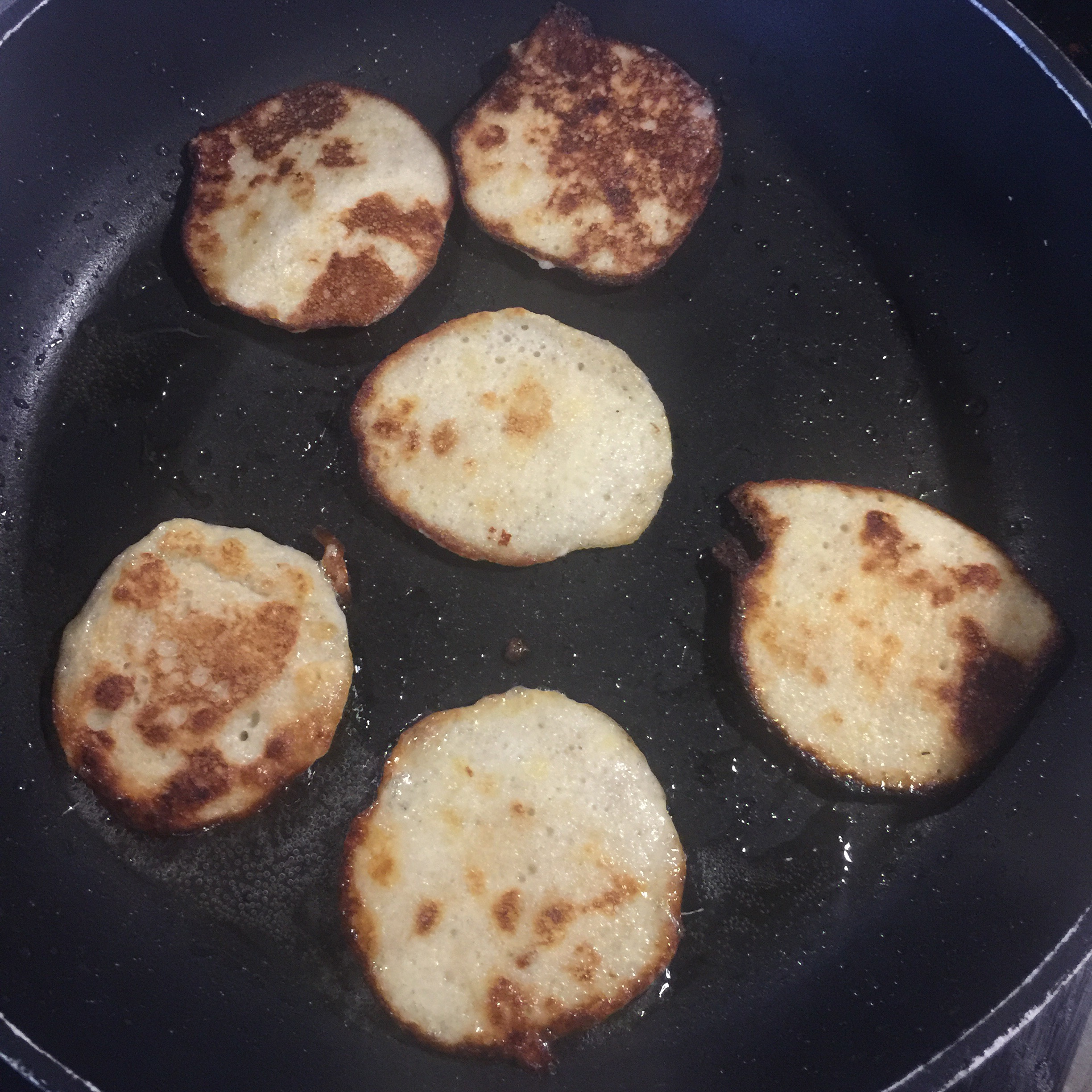 six baby led weaning banana pancakes in the frying pan after being flipped