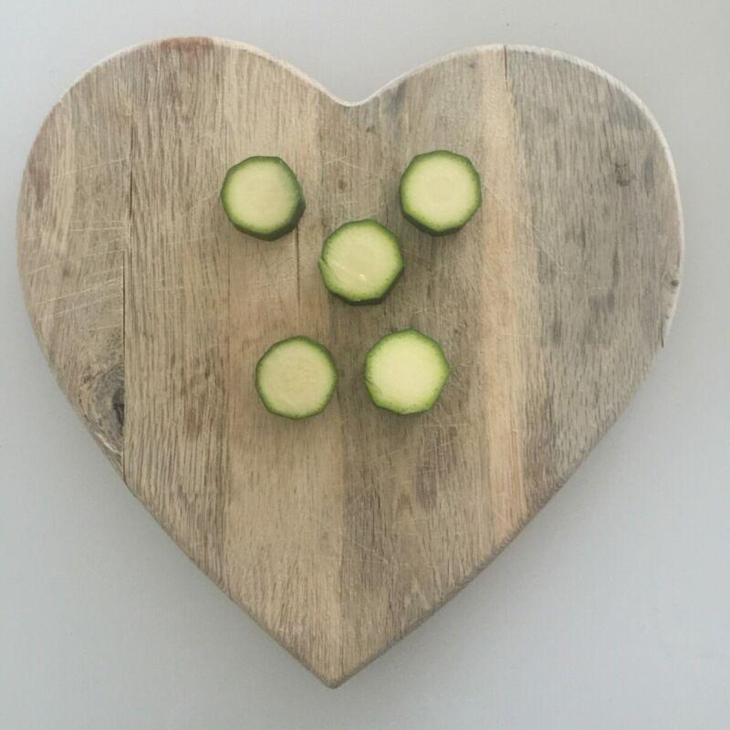 Sliced zucchini on a heart shaped chopping board