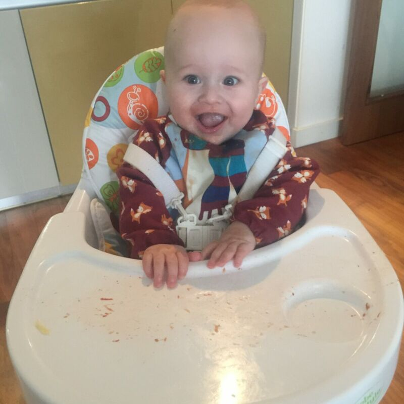 Dexter sat in his high chair after eating baby led weaning zucchini pizzas