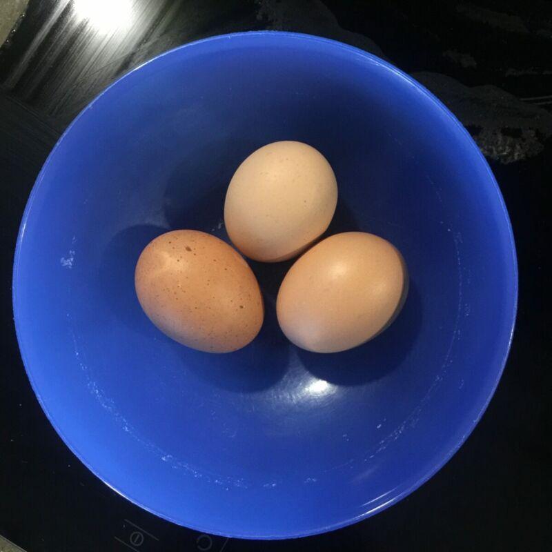 three eggs in a blue bowl
