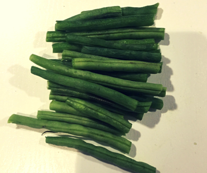 raw green beans, chopped sat on a white worktop