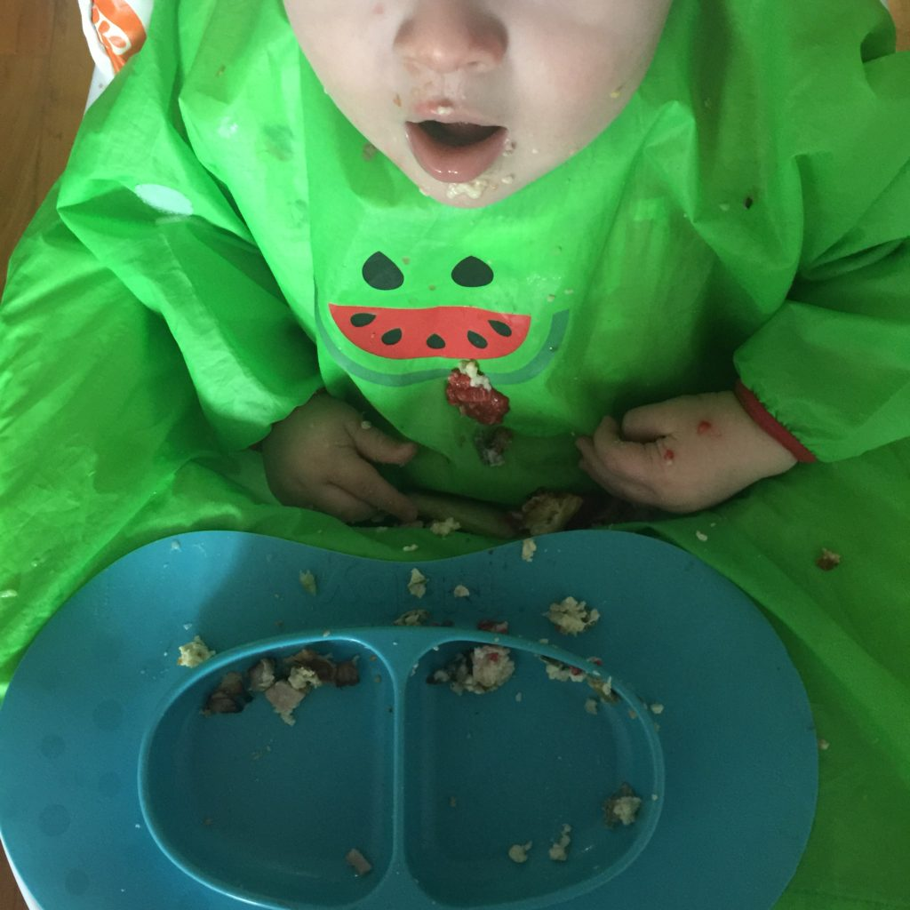 Dexter wearing his BIBaDO coverall bib with food all down it and a Nuby Sure Grip plate sat on the highchair