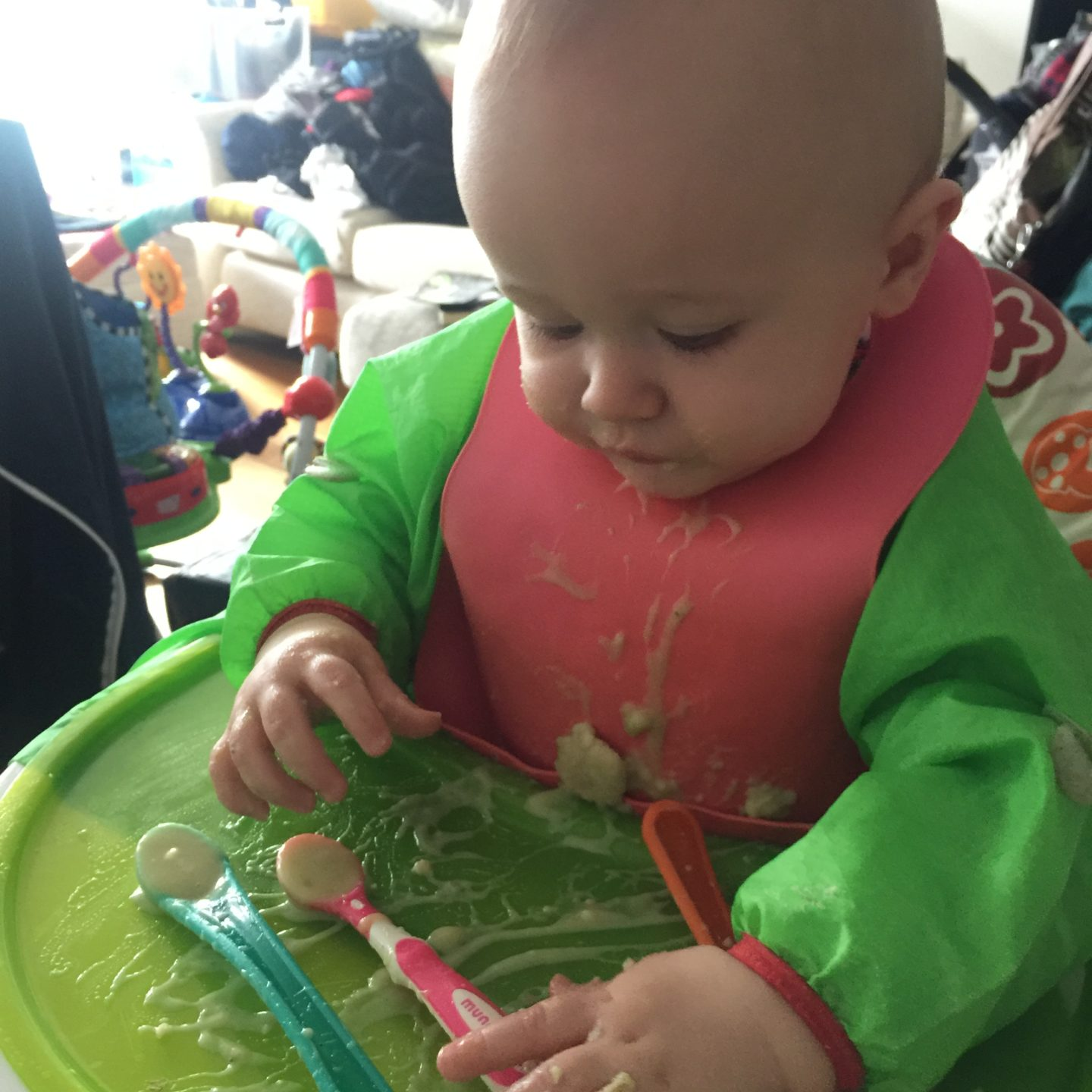 Dexter eating leek and potato soup from preloaded spoons while sat in highchair