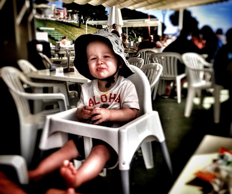 Dexter at eight months old in an ikea highchair wearing a sunhat at a busy bar in Mallorca