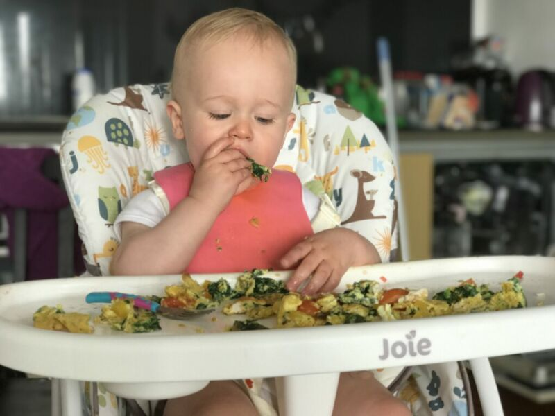 Dex sat on his joie mimzy snacker high chair putting his hand to his mouth