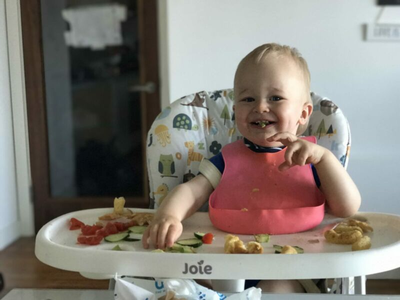 Dexter wearing a pink plastic bib, sat in his joie mimzy snacker highchair with food all over the tray