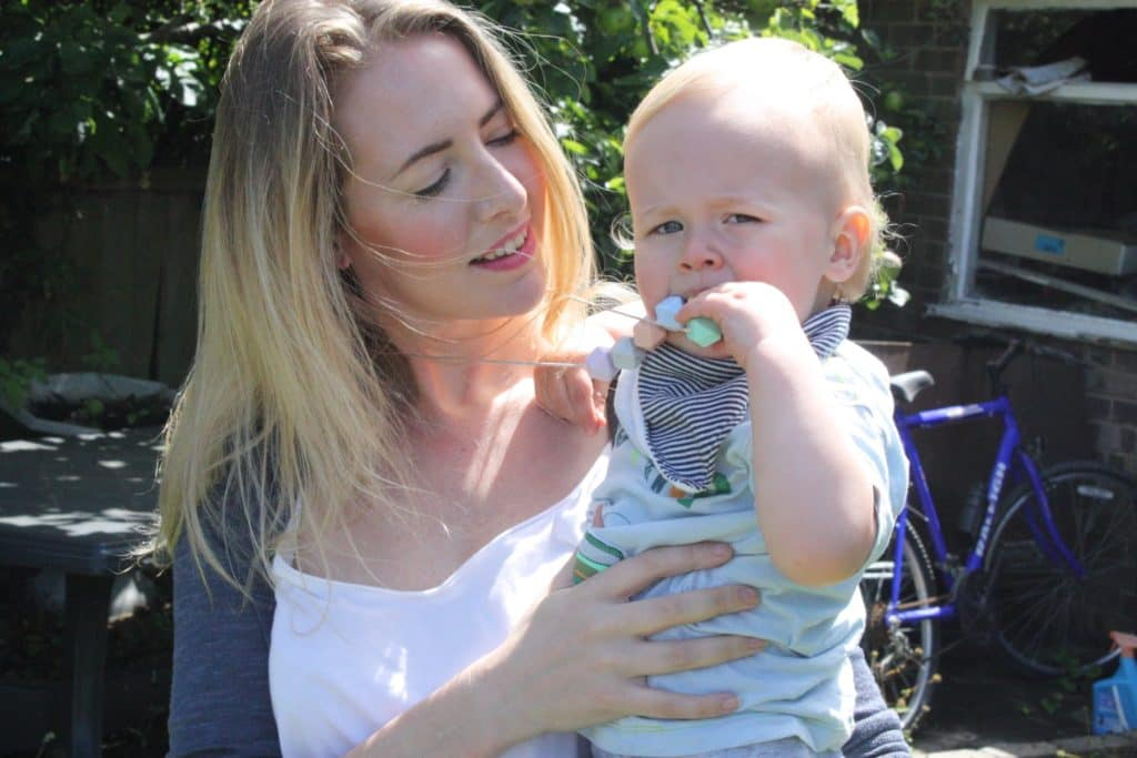 Nicola and Dexter in a garden, Nicola is hlding Dexter and wearing a Mama+Belle teethimh necklace which Dexter is putting in his mouth
