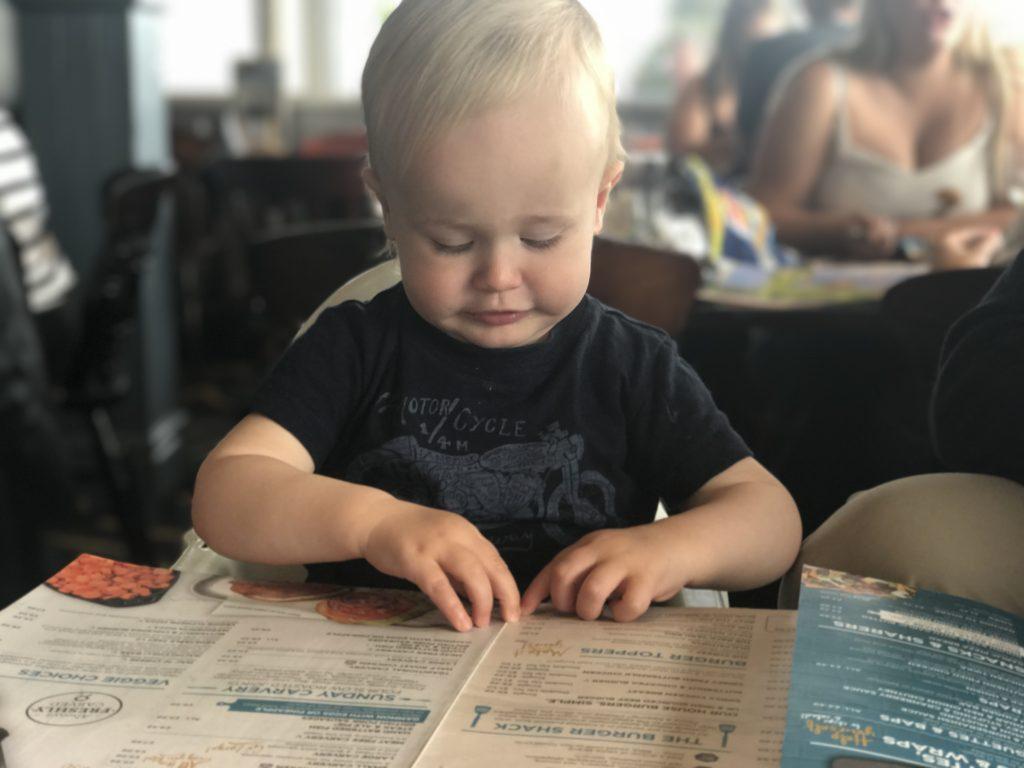 Dexter reading the menu sat in a highchair in the britannia inn liverpool