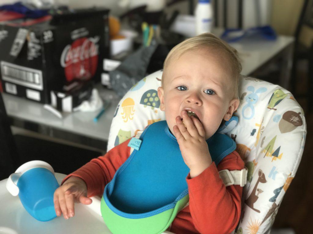 dexter sat at his high chair wearing a bibetta ultra bib and eating