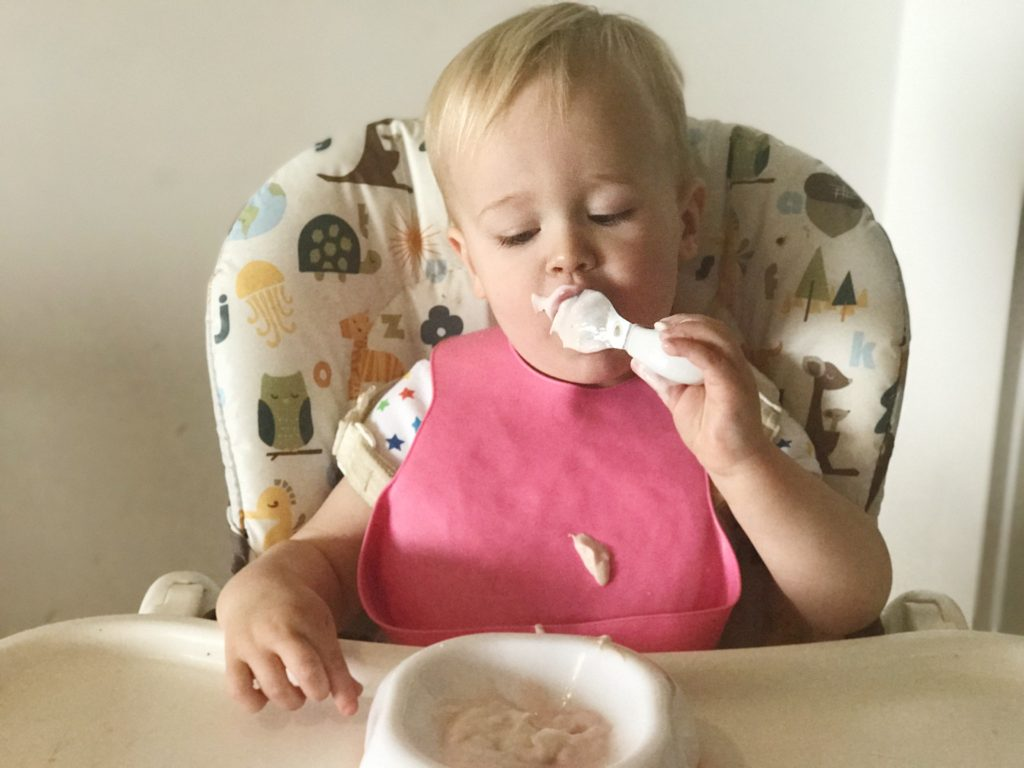 Dexter sat in his highchair, wearing a pink bib using Doddl cutlery to scoop yoghurt into his mouth