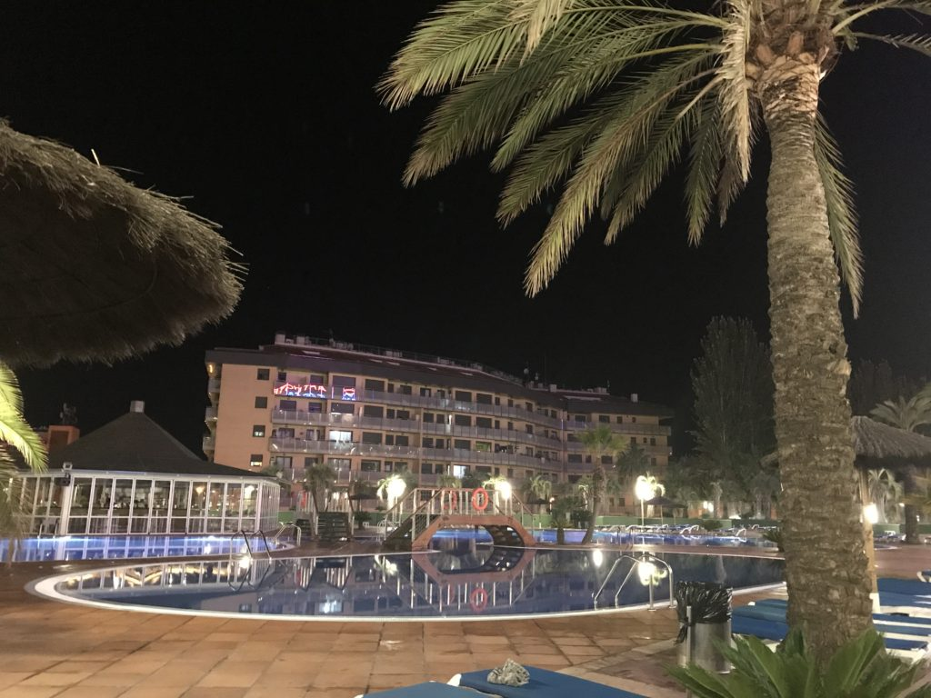 a view of the pool, palm trees and the costa encantada hotel at night