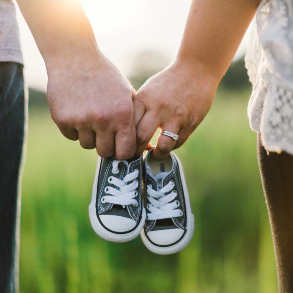 A man and woman stood in a field holding hands. Intertwined in their fingers is a pair of tiny baby shoes. When is the right time to have another baby?