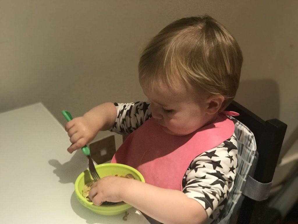 20 month milestones: dexter eating a bowl of noodles sat at the table in his booster seat