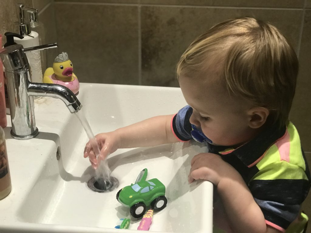 20 month milestones: dexter playing with water running from the tap into the sink