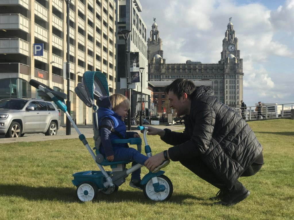 Dexter on his little tikes 4 in 1 trike infront of the liver building looking at his dad who is kneeling in front of him