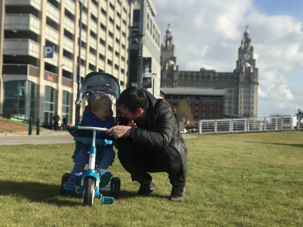 Dexter on his little tikes 4 in 1 trike in front of the liver building laughing with his dad who is next to him