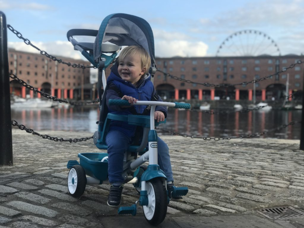 Dexter in front of the iconic albert dock on his little tikes 4 in 1 trike