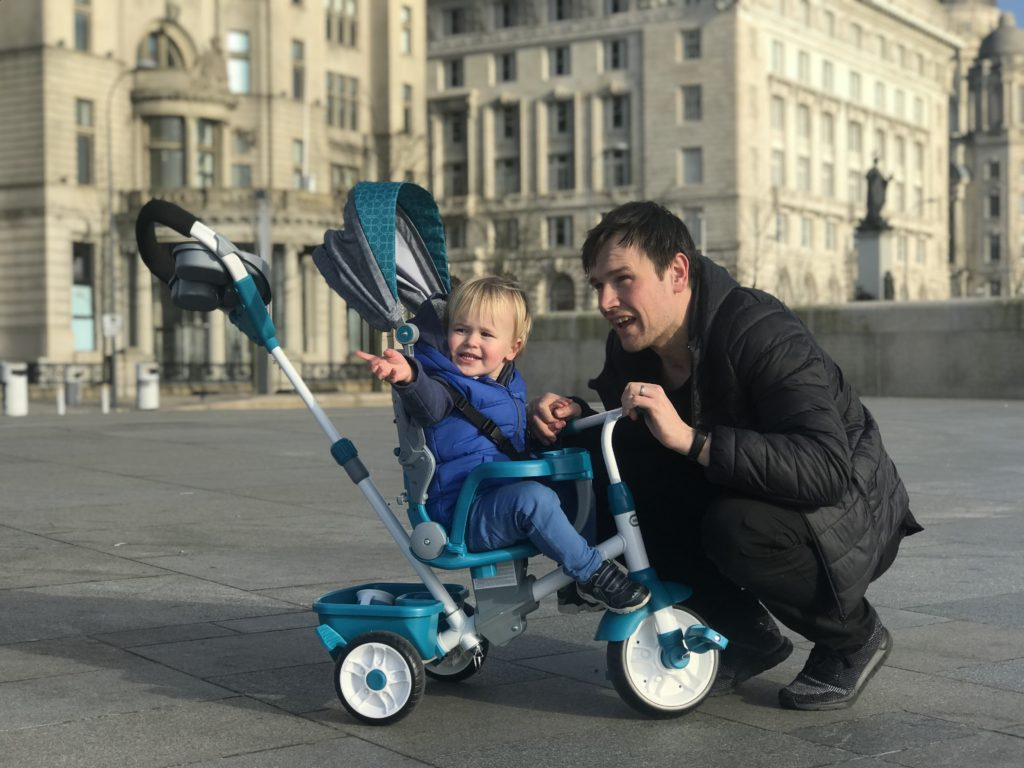 Dexter on his little tikes 4 in 1 trike infront of the liver building next to his dad pointing something out to him