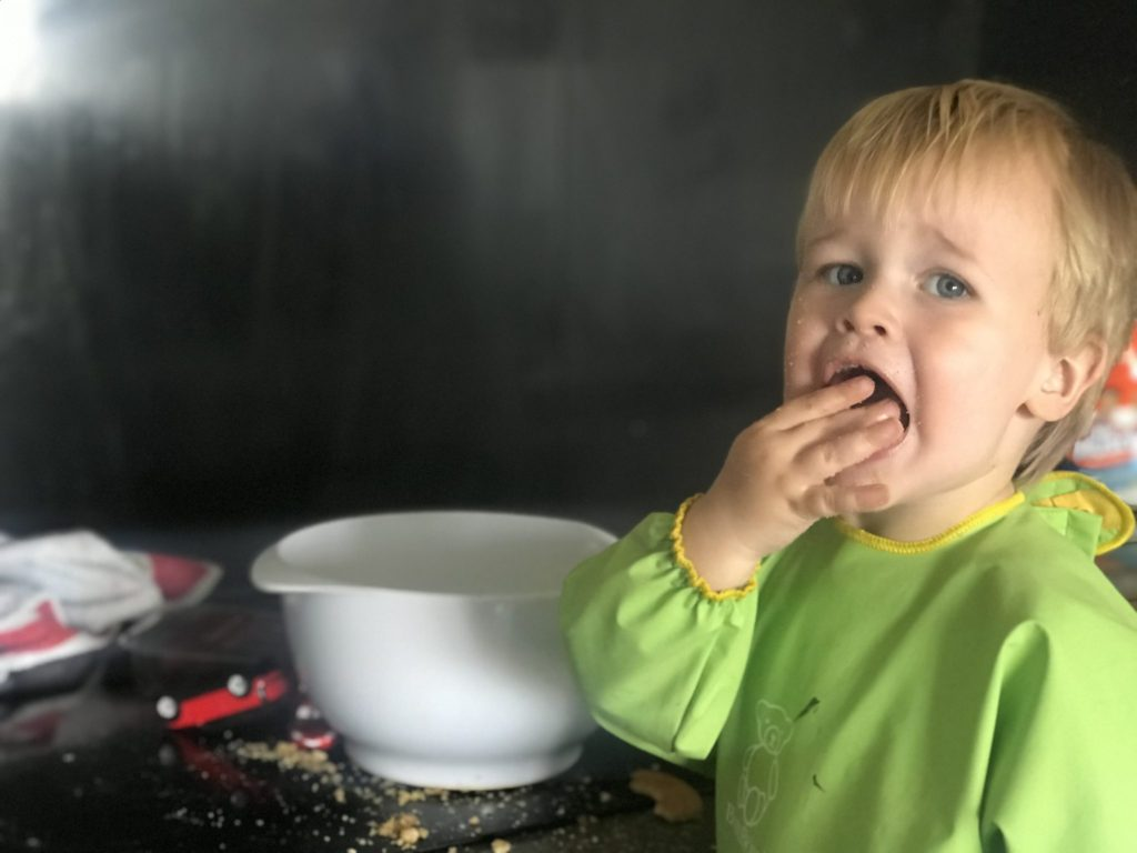 Dexter stood in the kitchen next to a white bowl and lots of crumbs, shoving a cookie in his mouth while wearing a baby bjorn long sleeved bib