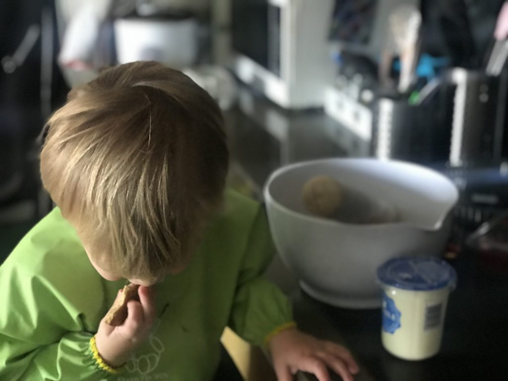 Dexter stood at the kitchen worktop next to a white bowl and cream, putting a cookie in his mouth and wearing a baby bjorn long sleeved bib