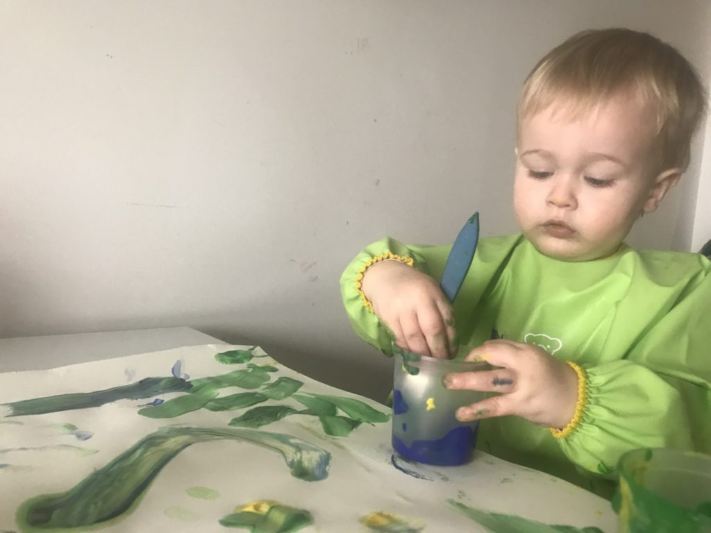 Dexter sat at the table painting wearing a baby bjorn long sleeved bib
