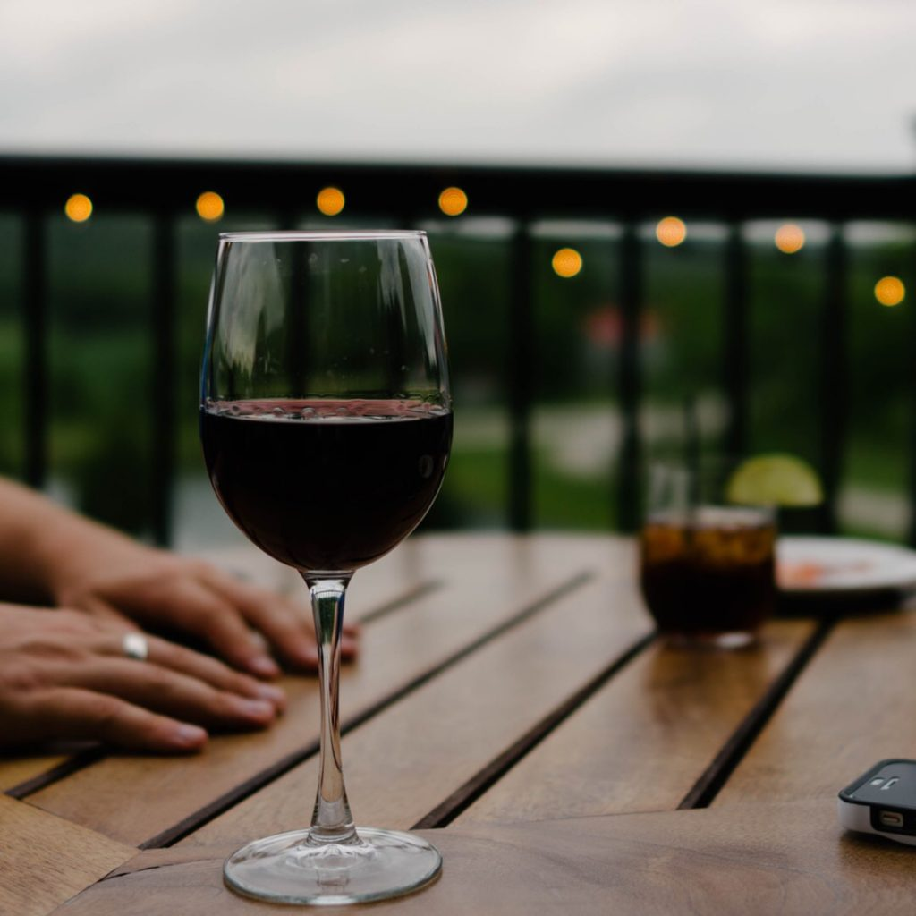 glass of red wine on a wooden table outdoors with fairy lights on the fence