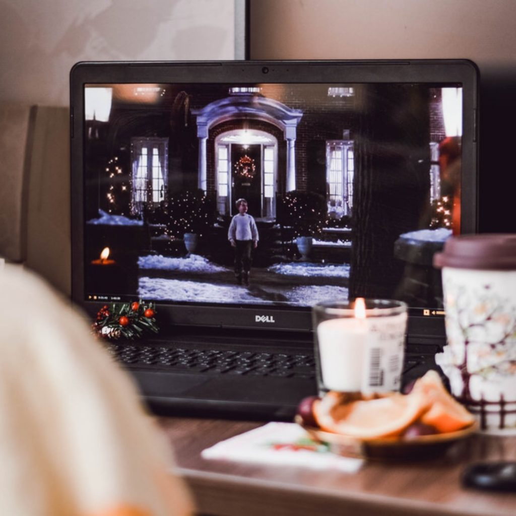 laptop showing christmas movie with a candle and cup of coffee in front of it