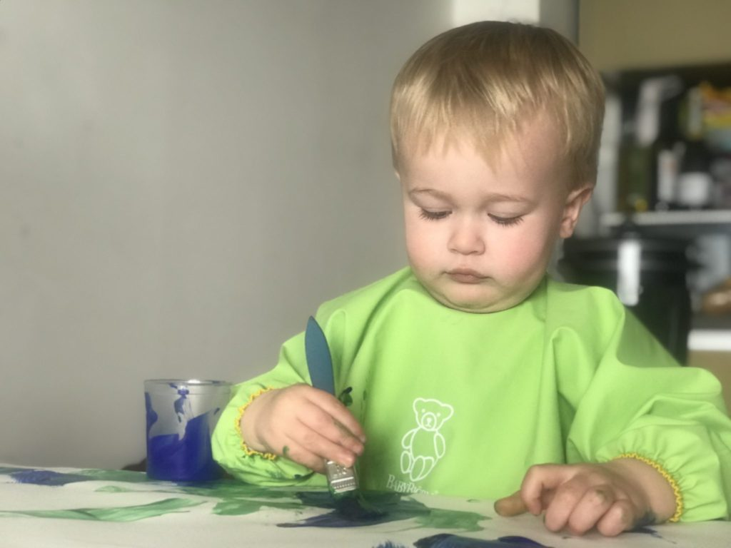 Dexter painting while wearing the Baby Bjorn long sleeved bib