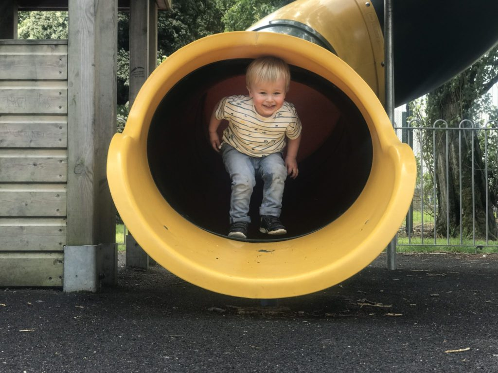 dexter walking out of a yellow tubeslide wearing jeans and a t-shirt