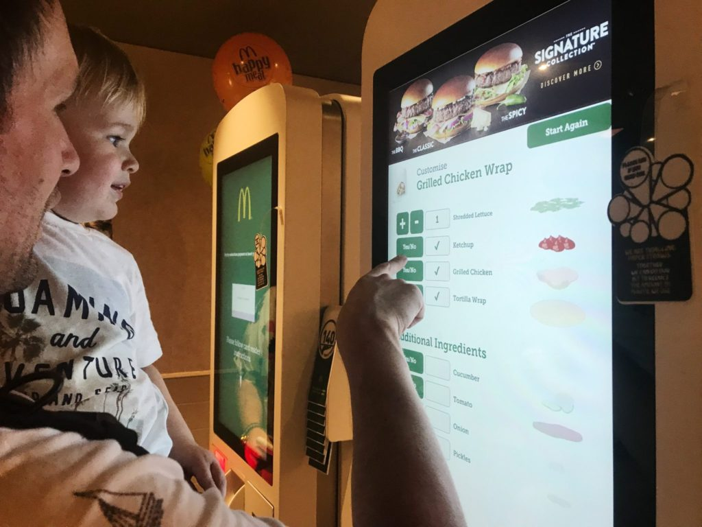 Neil and Dexter using a self service kiosk to order a McDonalds grilled chicken wrap