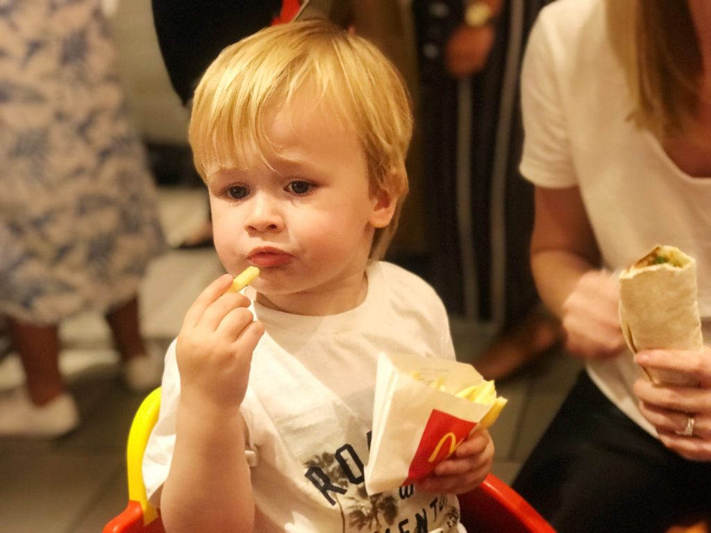 Dexter eating McDonalds fries while I hold a McDonalds grilled chicken wrap