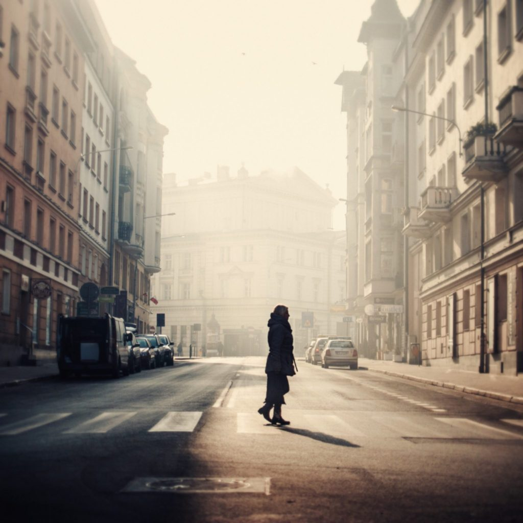 Woman stood on a zebra crossing on a foggy street
