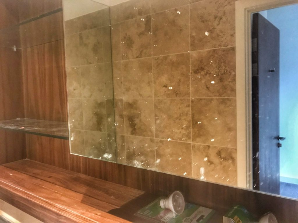 our bathroom before the end of tenancy clean with dirty shelves and a stained mirror