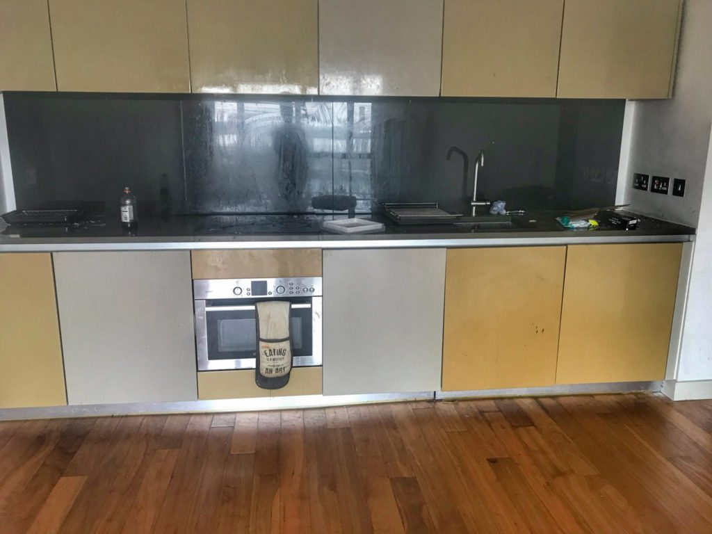 our kitchen before the end of tenancy clean showing dirty kitchen cupboards and a stained and greasy splashback
