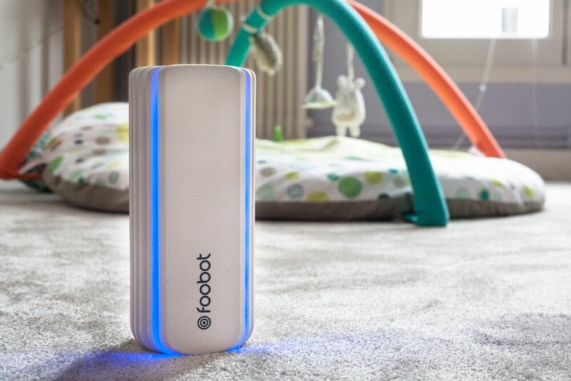 Foobot air quality monitor sat on a carpet with a baby's playmat in the background