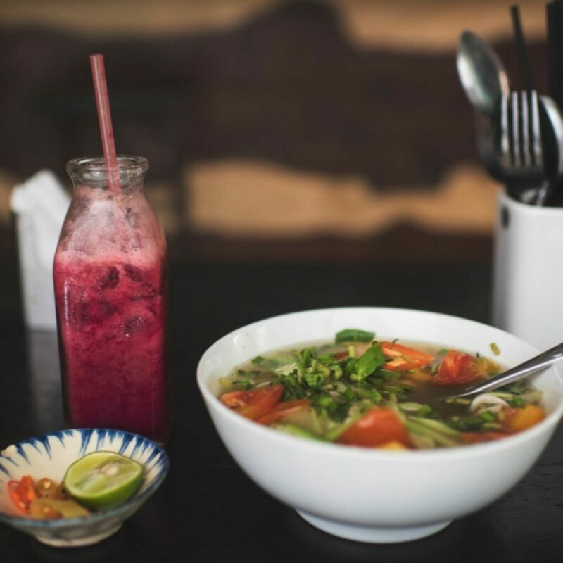a bowl of vietnamese food along with a pink drink served in a bottle