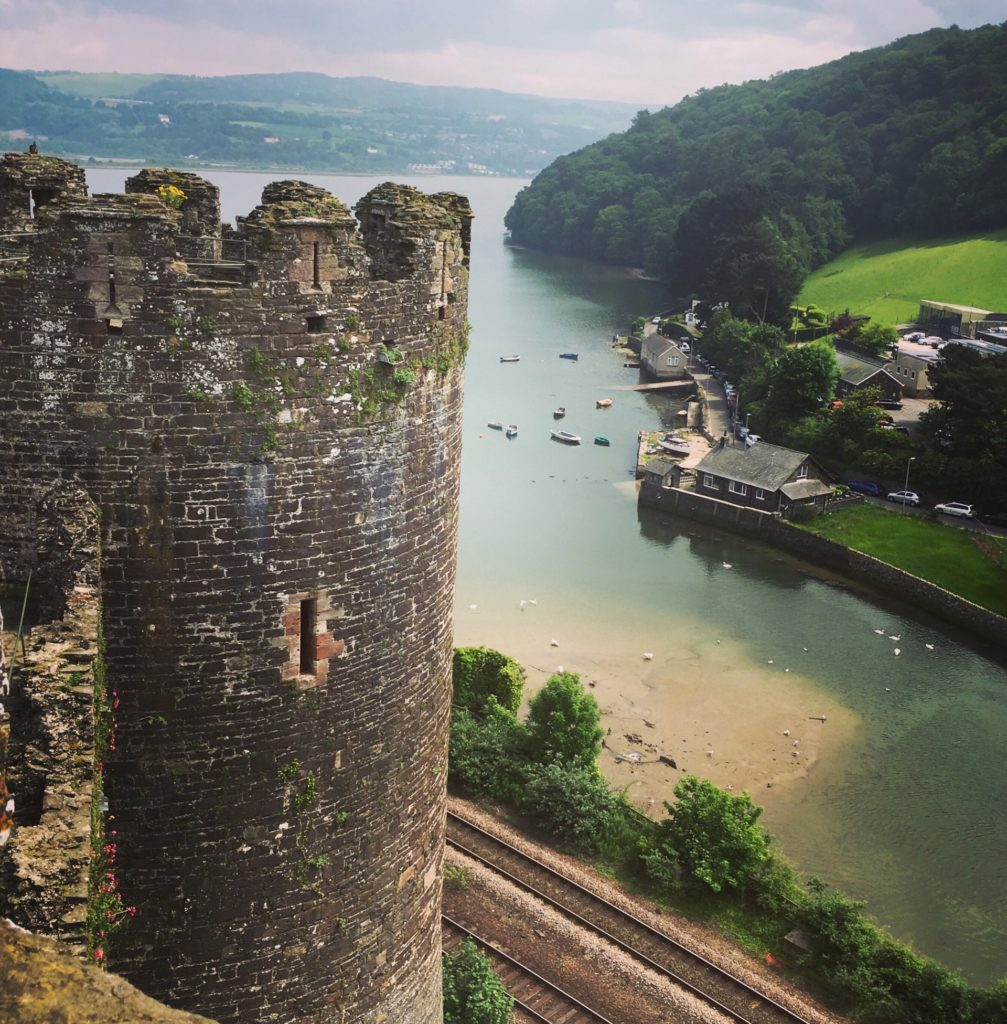 Conwy marina from the top of Conwy castle. A castle turret to the left and golden sands and green waters below