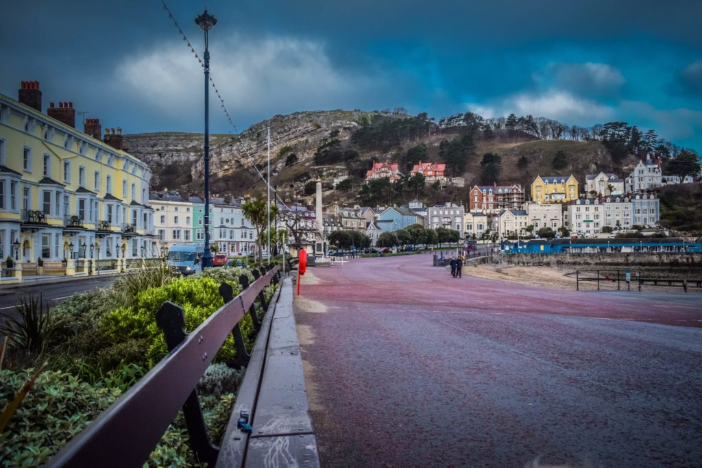 Llandudno promenade, one of North Wales towns. Coloured hotel buildings to the left, the Great orme directly ahead and the pier to the right