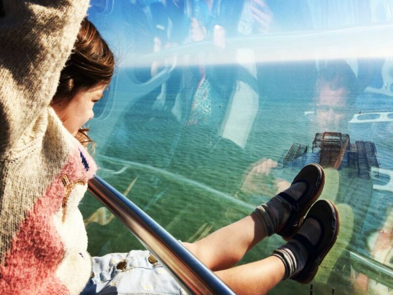 girl on british airways i360 tower with her legs against the glass looking out to sea