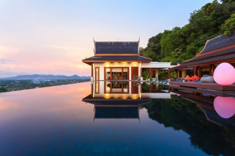 a villa in phuket next to an infinity pool with mountains in the distance