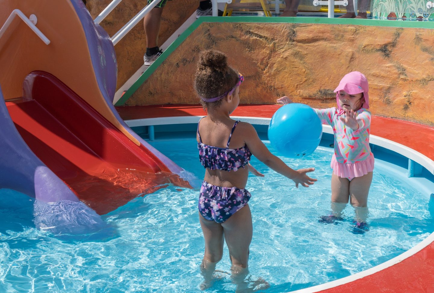 two girls playing in a small swimming pool in phuket passing a blue ball between them
