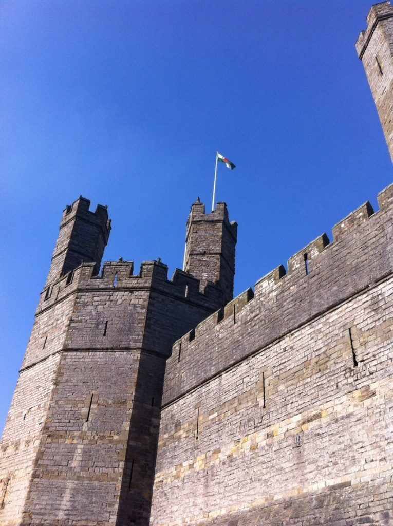 Caernarfon castle from below, looking up to two turrets and a welsh flag