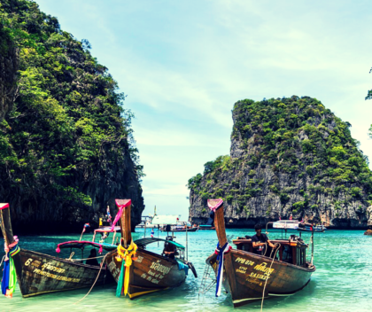 three boats on the green waters of thailand