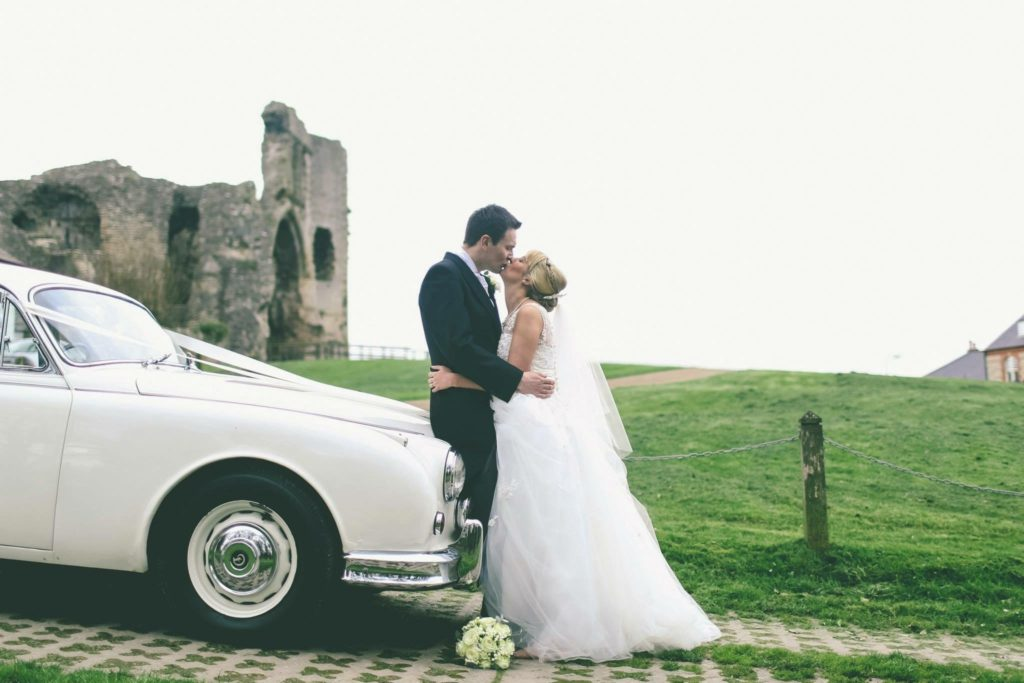 Nicola and Neil on their wedding day embracing while leaning on a white classic car with Denbigh castle to the left in the distance