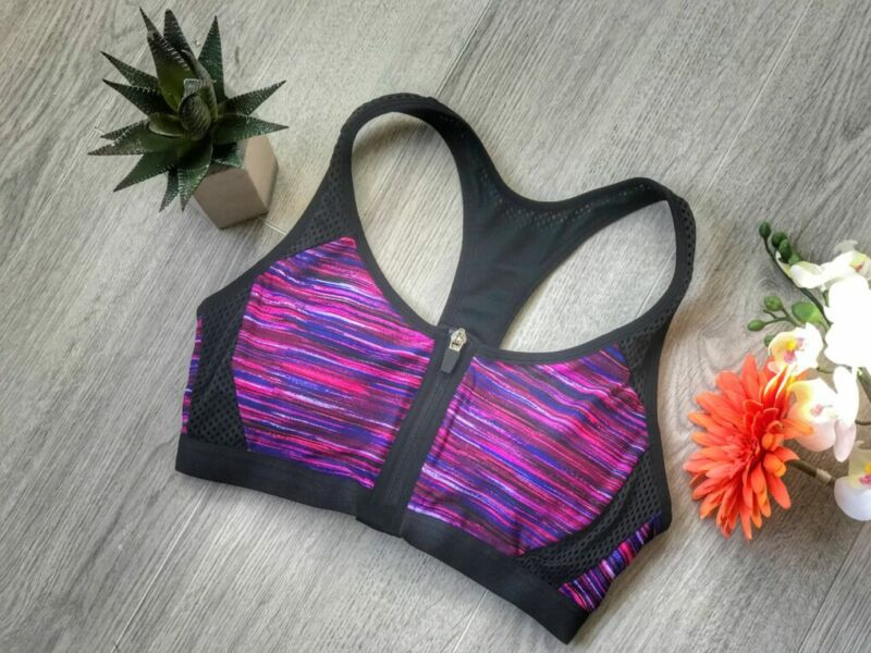 a purple and black zipped front maternity lingerie sport bra flat lay on floor with cactus and orange flower