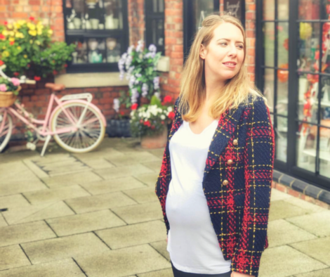 A pregnant woman wearing a red and black jacket, clearly pregnant and looking out into the distance