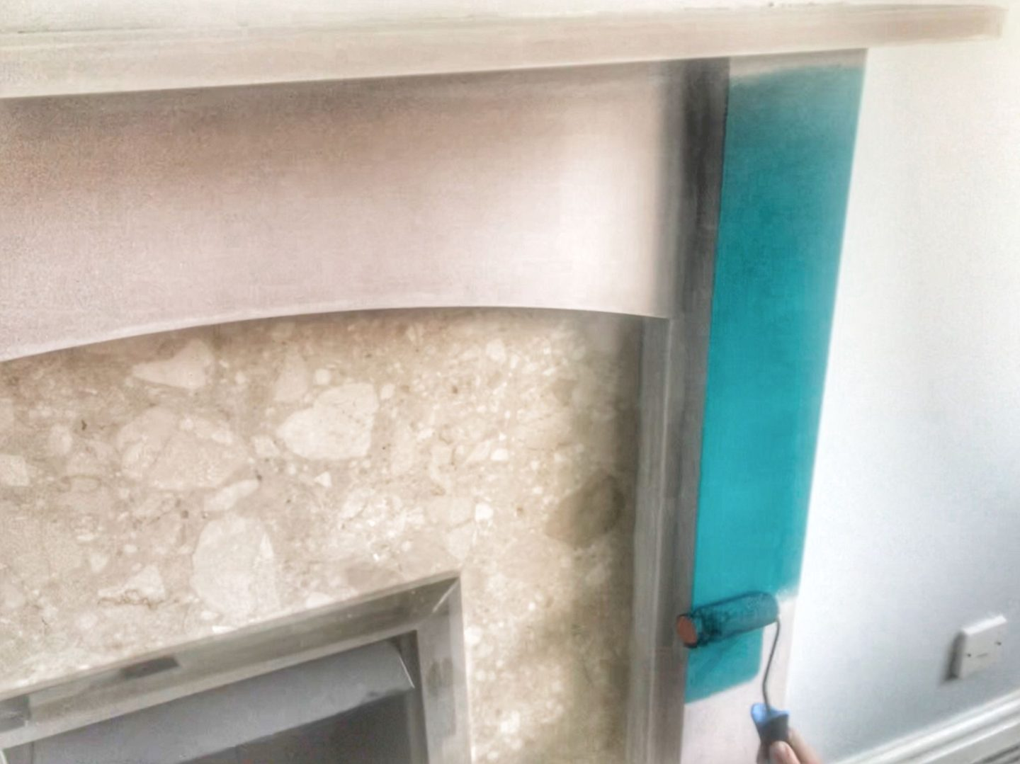 painting a fireplace with the teal paint using a roller