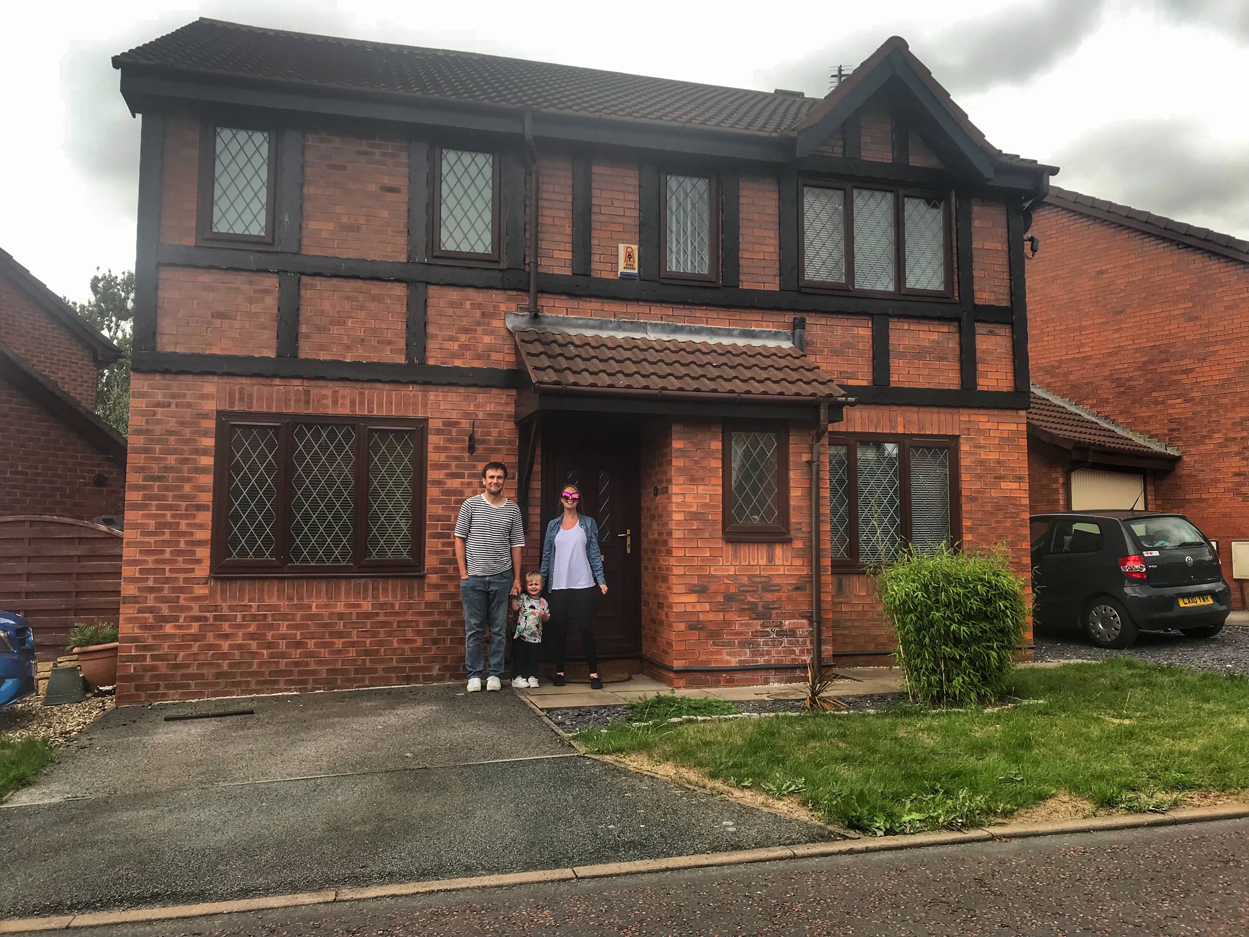 Nicola, her husband and toddler stood in front of their house - a four bed detached property with two driveways