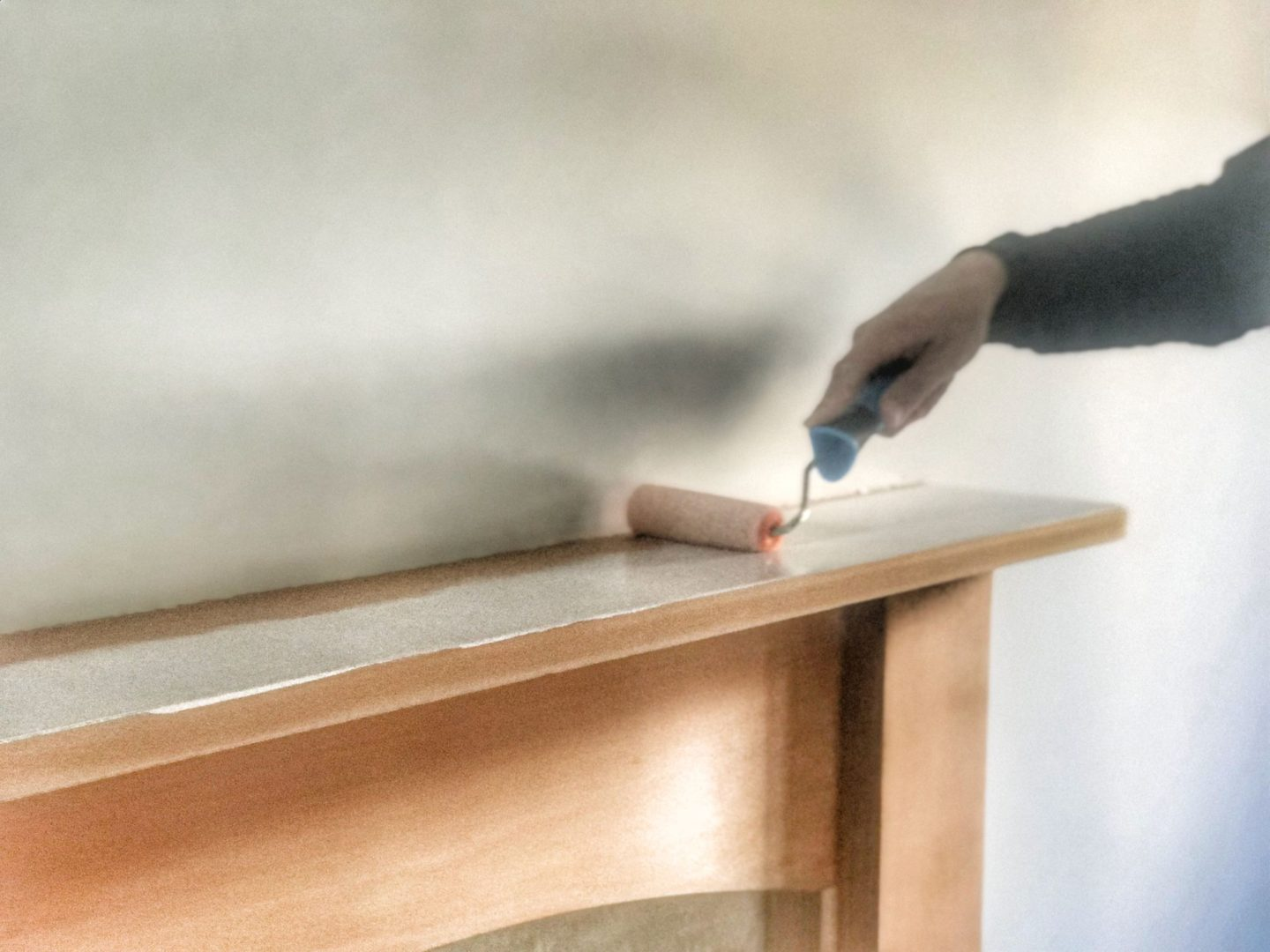 painting a fireplace with the primer using a roller